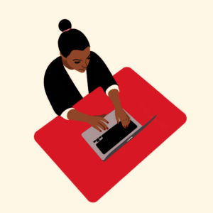 An image of a dark-skinned woman who is seated at a red table, typing on her laptop.