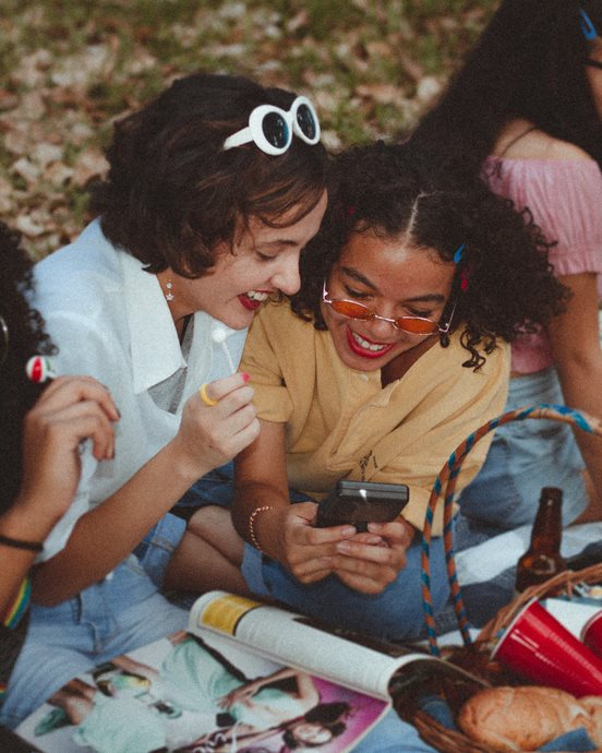 An image of four teenage girls having a picnic in a field. They are huddled over a cell phone, laughing.