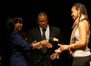 An image of two Black women who are standing on a stage, about to shake hands, with a Black man standing slightly behind them in the middle. The young woman on the right seems to be accepting an award.
