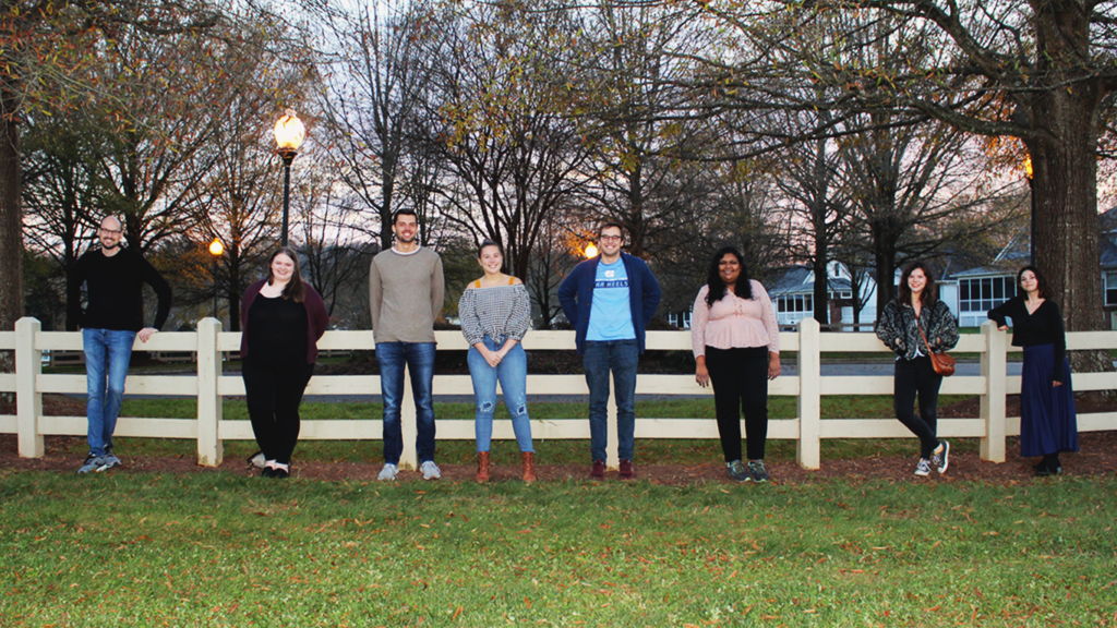 An image of eight members of the lab team, including the lab director, graduate students, lab managers, and the research programmer. They are outside, leaning against a white fence, and smiling.
